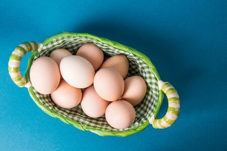 Top view, flat lay. Farm brown eggs in a wicker basket lined with checkered fabric. Blue background. Copy space.