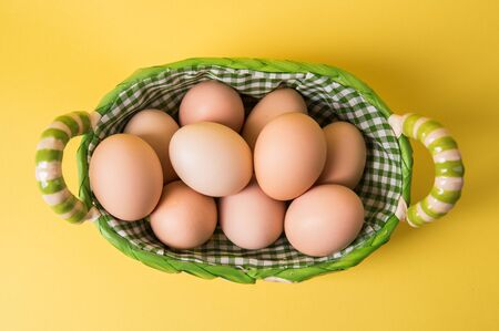 Top view, flat lay. Farm brown eggs in a wicker basket. Yellow background.