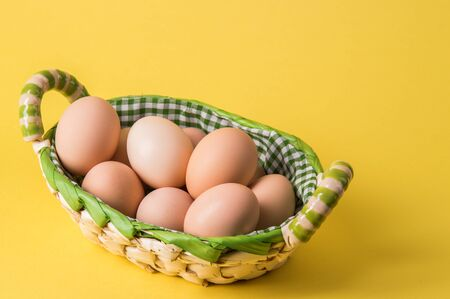 Close up, macro. Rustic brown eggs in a wicker basket lined with checkered fabric. Yellow background. Copy space.