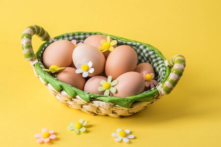 Close up. Easter still life. Rustic brown eggs in a wicker basket lined with checkered fabric. The decor of the felt flowers of pastel colors. Yellow background. 写真素材
