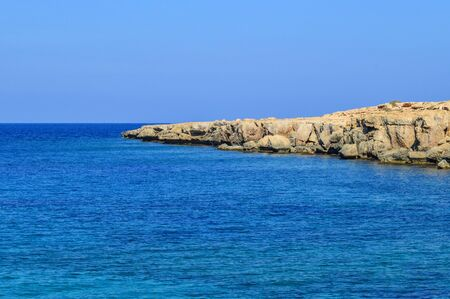 Island of Cyprus. Mediterranean coastline. Beautiful day, blue sky, foamy waves of the azure sea roll to the rocky shore. Background. Copy space.