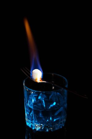 Close up, macro. A glass of alcohol, on it lies a fork with a cube of sugar. Sugar is engulfed in flames of burning fire. Low key. Black background. Copy space.