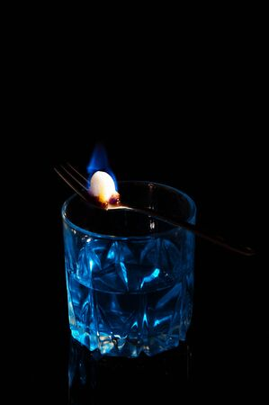 Close up, macro. A glass of blue alcohol, on it lies a fork with a piece of sugar. Sugar is consumed by fire and caramelized. Low key. Black background. Copy space.