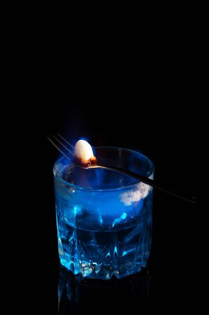 Close up, macro. A glass of blue alcohol, on it lies a fork with a piece of sugar. Sugar burns and caramelizes. The fire set fire to the surface of the drink. Low key. Black background. Copy space. Reklamní fotografie