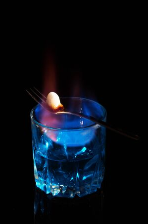 Close up, macro. A glass of absinthe, on it lies a fork with a piece of sugar. Sugar is consumed by fire and caramelized. Low key. Black background. Copy space. Reklamní fotografie