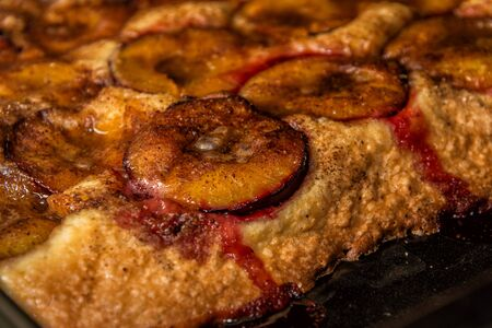 Close up. A piece of fragrant homemade plum cake on a black baking tray, sticking out from the oven. Standard-Bild - 134793603