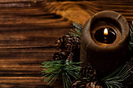 Close up, macro. A lit brown candle is decorated with a spruce branch with small cones. Brown wooden boards on the background. Copy space. Stockfoto
