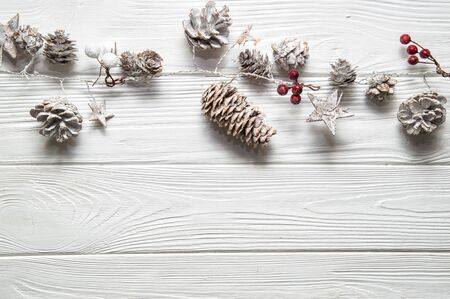 Top view, flat lay. Christmas white background. Rustic garland with fir cones, red berries and snowy stars. Copy space below.