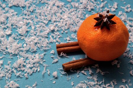 Close up, macro. Orange mandarine in aniseed hat skiing out of cinnamon. Deep blue background with artificial snow. Copy space. 写真素材