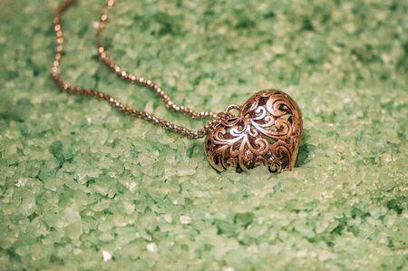 Close up, macro. Vintage ornate medallion lies on a background of large greenish sea salt.