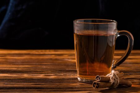 Close up. Black aromatic tea in a glass transparent cup. Rustic brown wooden background. Copy space.