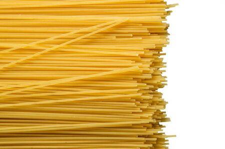Close up, macro. Top view, flat lay. Uncooked yellow long spaghetti isolated on white background. Spaghetti laid out diagonally. Copy space. Stock Photo