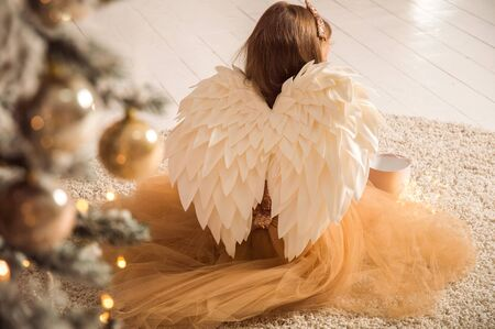 Close up. Christmas concept. View from the back of a child in the image of a Christmas angel.