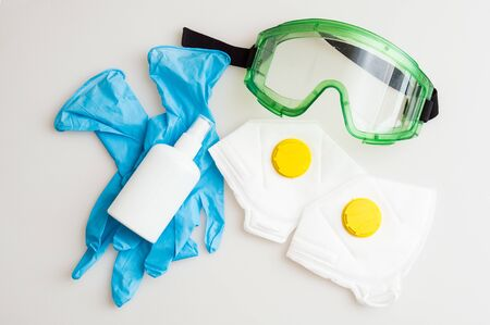 Close up. Essentials during Coronavirus Pandemic COVID-19. Respirators with a yellow valve, protective glasses, rubber gloves, sanitizer on white background.