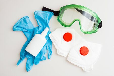 Close up. Essentials during Coronavirus Pandemic COVID-19. Respirators with a red valve, protective glasses, rubber gloves, sanitizer on white background. Imagens