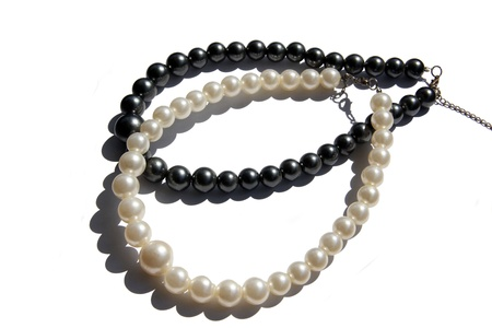 textille: Necklaces from black and white pearls on a white background