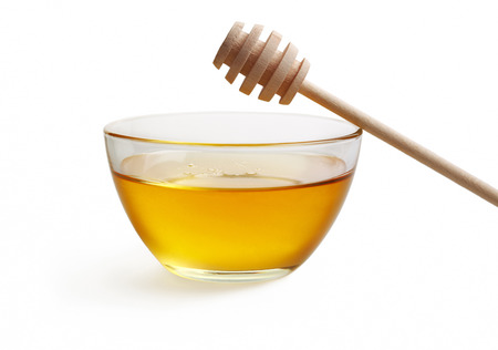 Glass bowl with floral honey and stick isolated on white background. photo