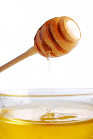 Honey dripping from a wooden dipper in glass bowl. photo