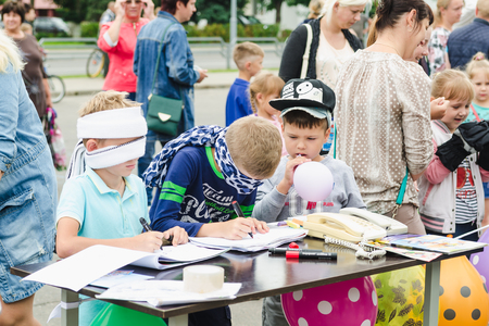 HORKI, BELARUS - JULY 25, 2018: Two small blindfolded boys draw on paper on a table and one little boy inflates a balloon on a summer day in a crowd.