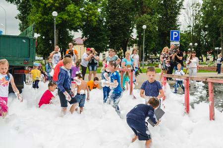 HORKI, BELARUS - JULY 25, 2018: Children of different ages play with airy white foam at the Rescue Service 112 holiday amid a crowd on a summer day. Editorial