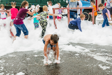HORKI, BELARUS - JULY 25, 2018: Children of different ages play with white foam in the park at a party in the afternoon in a crowd of people