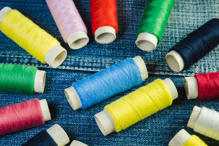 Spools of blue,white, pink, red and green sewing thread on blue denim