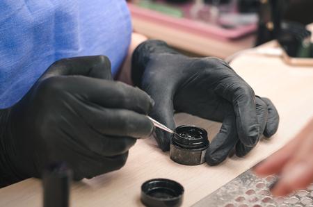 Manicurist in black latex gloves dips a brush in black gel polish