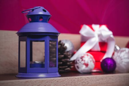 Violet old aromatic lamp on the background of Christmas decorations and gifts. Cozy home holiday decor