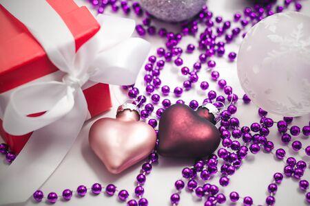 Dos adornos navideños de vidrio en forma de corazón de color rosa y morado, una caja de regalo roja con una cinta blanca y perlas de color lila sobre una superficie clara