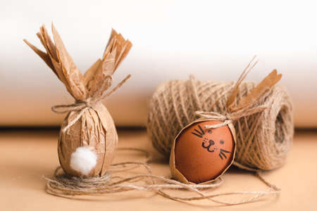 Gift Easter eggs in brown craft paper in the shape of a rabbit and a skein of jute threads