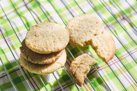 Round homemade shortbread cookies with sesame seeds cool down on a wire rack