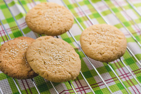 Homemade round shortbread cookies with sesame seeds on a wire rack Standard-Bild