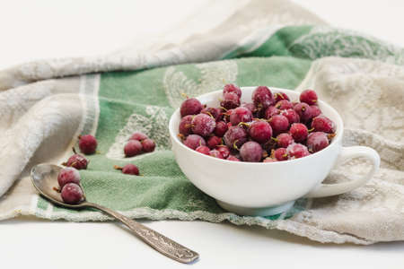 Frozen berries of red gooseberries with hoarfrost in a white cup and a spoon on an old linen tablecloth Standard-Bild