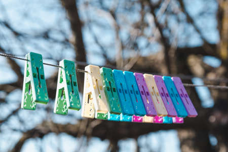 Multicolored beautiful clothespins on a clothesline for drying clothes, selective focus