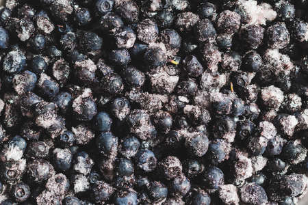 Frozen blueberries with ice crystals, background