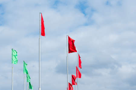 Flagpoles with red and green flags on cloudy sky background