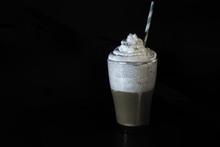 multilayer coffee or cappuccino in a glass cup with whipped cream