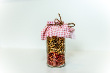 Homemade sun dried red and green peppers in a glass jar