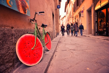 Old bicycle with watermelon wheels near the wall of the building