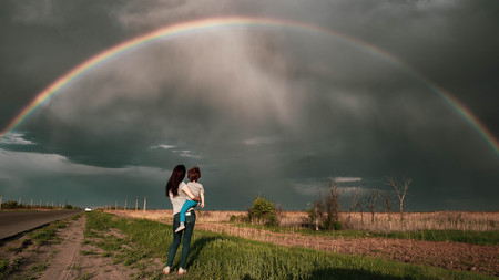 Rainbow over field with people. Mom and son look at the rainbow