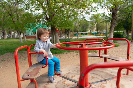 boy on the playground rides on a swing Stock fotó