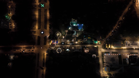 Children playground on yard activities in public park in the night lights. Aerial view