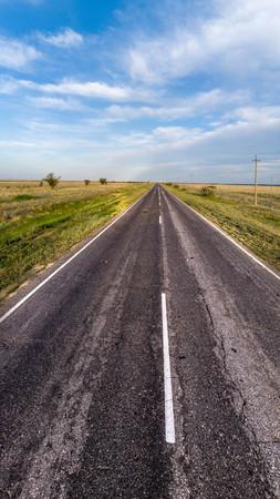 La strada asfaltata vuota va in lontananza