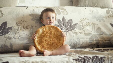 boy with uzbek cake on the couch at home