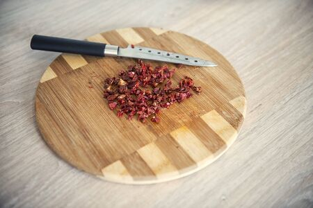 Dry tomatoes finely chopped on a cutting board
