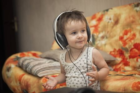 Charming boy listening to music in headphones