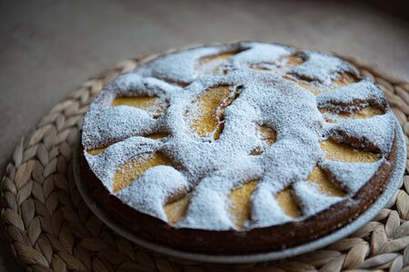 Russian charlotte with blur on the sides and peach and icing sugar. Ornament of peach slices