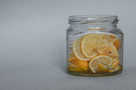 Thinly sliced lemon with sugar in a glass jar