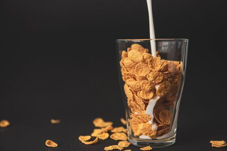 cornflakes with milk in a transparent glass against a black background