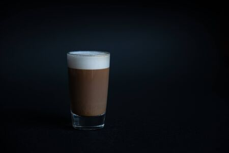 mini cup of cappuccino in a glass cup on black background with copyspace